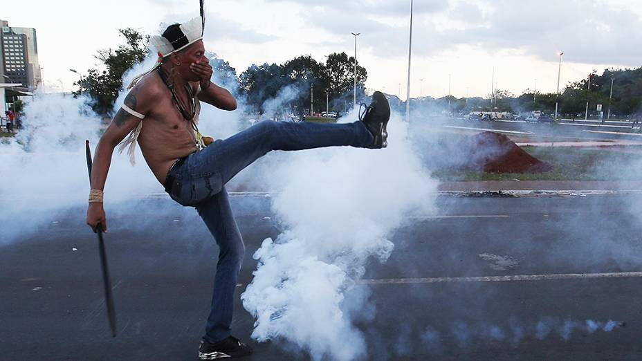 Manifestante chuta uma bomba de gás lacrimogênio lançada pela polícia, durante protesto dos índios em Brasília