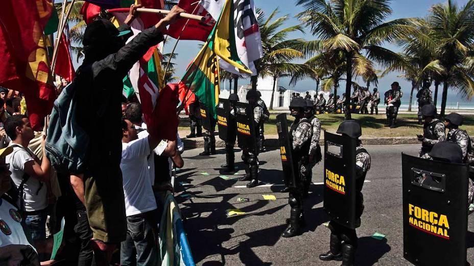 Manifestantes protestam em frente a homens do Exército nos arredores do Hotel Windsor, na Barra da Tijuca
