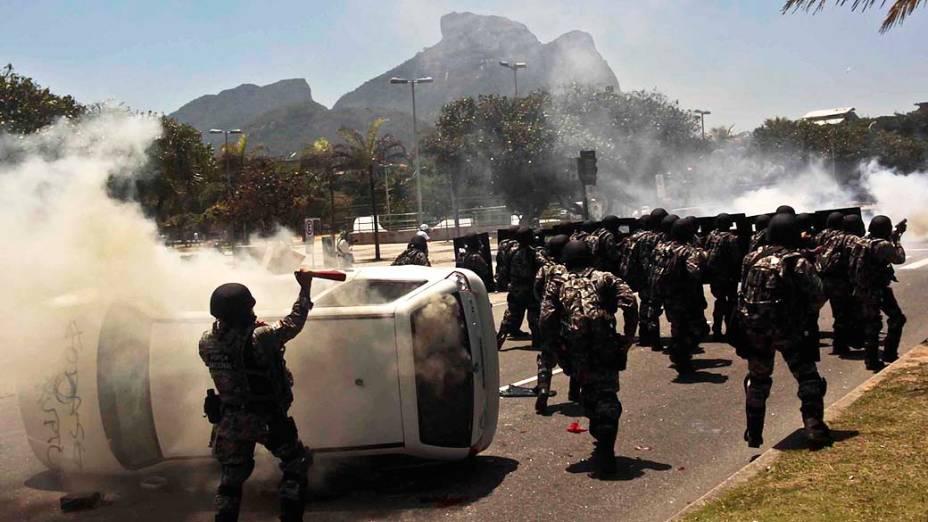 Manifestantes viram carro de emissora de TV e entram em confronto com homens da Força Nacional, nos arredores do Hotel Windsor, no Rio