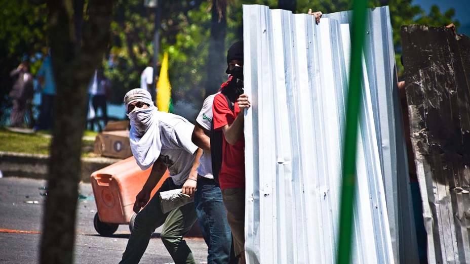 Manifestantes entram em confronto com integrantes da Força Nacional e o Exército na entrada do hotel Windsor Barra, zona oeste do Rio de Janeiro, onde acontece na tarde desta segunda-feira o leilão do campo de pré-sal de Libra