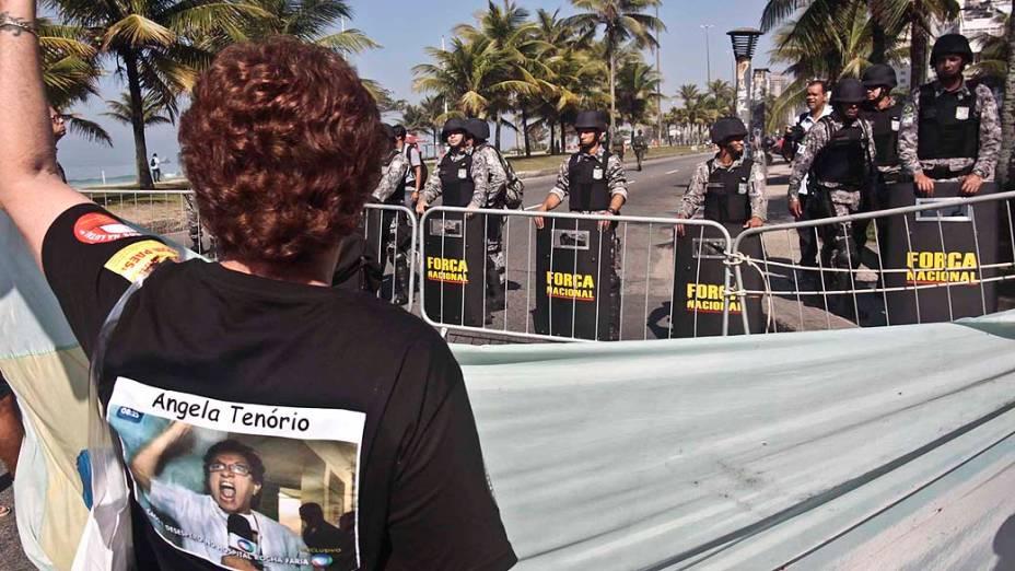 Manifestante protesta diante dos homens da Força Nacional que fazem a segurança do hotel em que será realizado o leilão de Libra, nesta segunda