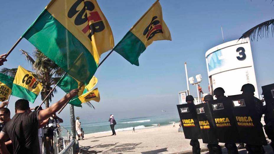 Manifestantes protestam em frente ao bloqueio feito pelas tropas do exército nos arredores do hotel Windsor, na Barra da Tijuca, na zona oeste do Rio de Janeiro (RJ), onde acontecerá a primeira rodada do leilão do Campo de Libra, relativo a exploração do pré-sal