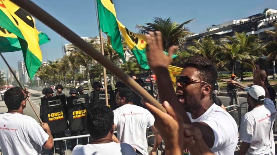 Manifestantes protestam diante dos homens da Força Nacional que fazem a segurança do hotel em que será realizado o leilão de Libra, nesta segunda