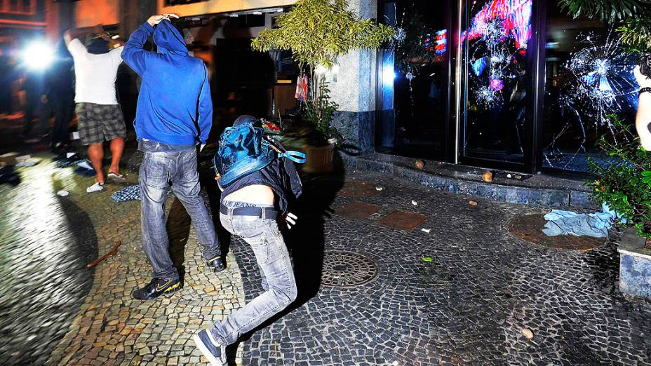 Vândalos atiram pedras em uma loja durante um protesto contra o governador do Rio de Janeiro, Sergio Cabral, na frente de sua residência no bairro do Leblon, no Rio de Janeiro