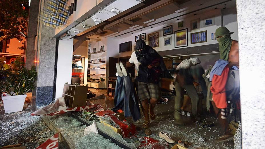 Vândalos saqueiam uma loja durante um protesto contra o governador do Rio de Janeiro, Sergio Cabral, na frente de sua residência no bairro do Leblon, no Rio de Janeiro