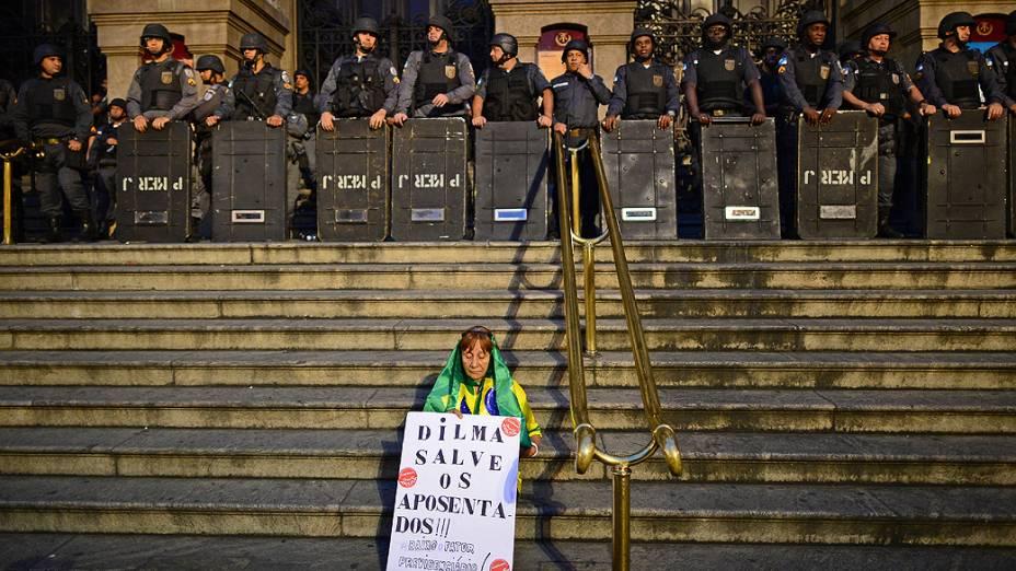 Rio de Janeiro - Mulher segura cartaz com uma mensagem para a presidente Dilma Rousseff, na escadaria do Teatro Municipal, nesta quinta-feira (11)