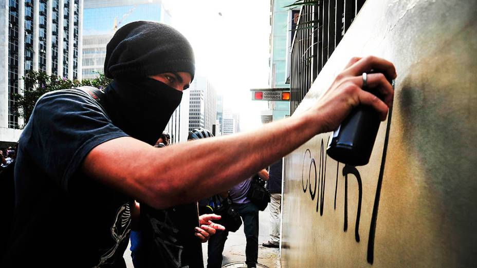 São Paulo - Integrante do Black Bloc faz pichação em muro durante manifestação na avenida Paulista
