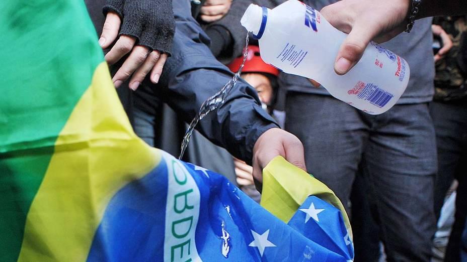 São Paulo - Manifestantes colocam alcool em uma bandeira do Brasil durante manifestação no centro da cidade