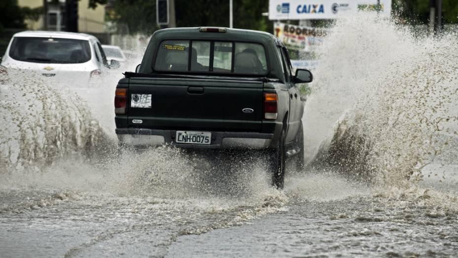 Caminhonete atravessa rua inundada no subúrbio do Rio de Janeiro, nesta quarta-feira (11)