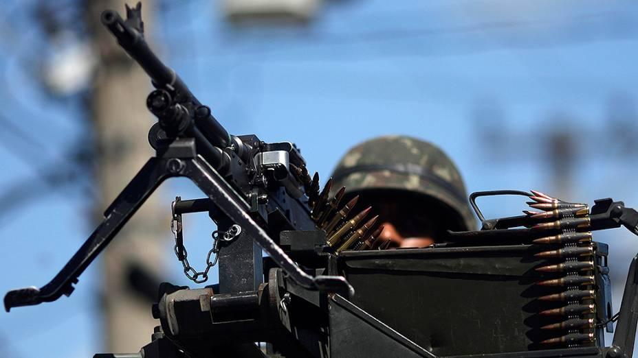 Soldado realiza patrulha em um blindado da Marinha no complexo de favelas da Maré no Rio de Janeiro