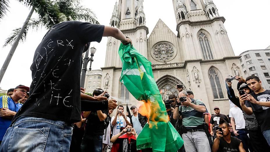 Manifestante queima uma bandeira do Brasil, durante a Marcha Antifascista na Praça da Sé, em São Paulo