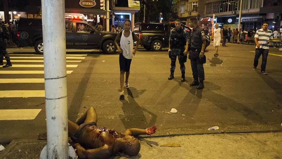 Mulher se aproxima de seu marido, Adilson Rufino da Silva, 34 anos, ferido durante um tiroteio com policiais na praia de Copacabana no Rio de Janeiro durante as comemorações do Ano Novo