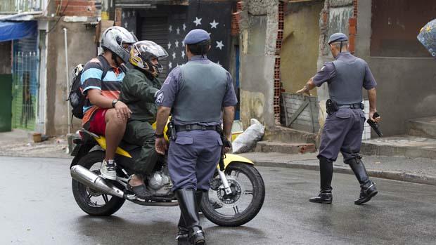 Policiais revistam motoqueiros na favela de Paraisópolis, em São Paulo