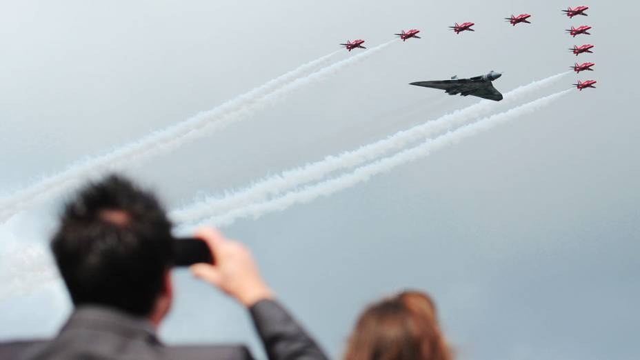 Os Red Arrows voam em formação ao lado do bombardeiro Vulcan para abrir oficialmente o Farnborough International Airshow, em Hampshire, sul da Inglaterra