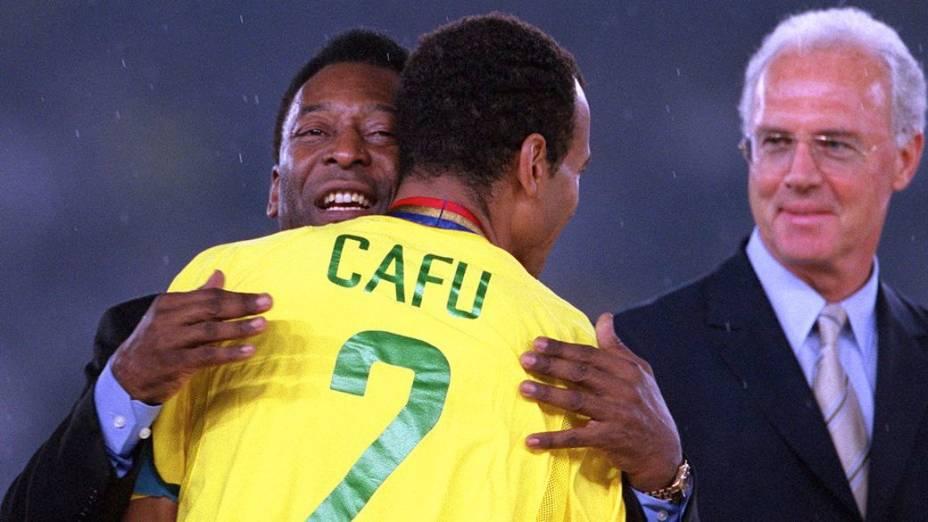 Pelé abraça Cafu antes de entregar a taça na conquista do penta, em 2002; ao lado deles, o alemão Franz Beckenbauer
