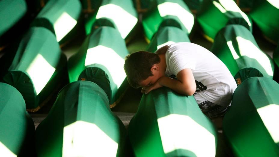 Na Bósnia-Herzegóvina, menino chora perto de caixões preparados para o enterro dos 520 corpos recentemente identificados das vítimas do massacre de Srebrenica, considerado o pior massacre da Europa desde a Segunda Guerra Mundial