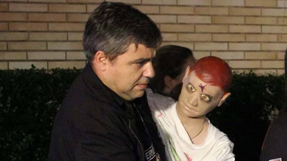 Policial carrega boneco que representou o executivo na reconstituição do crime, em São Paulo