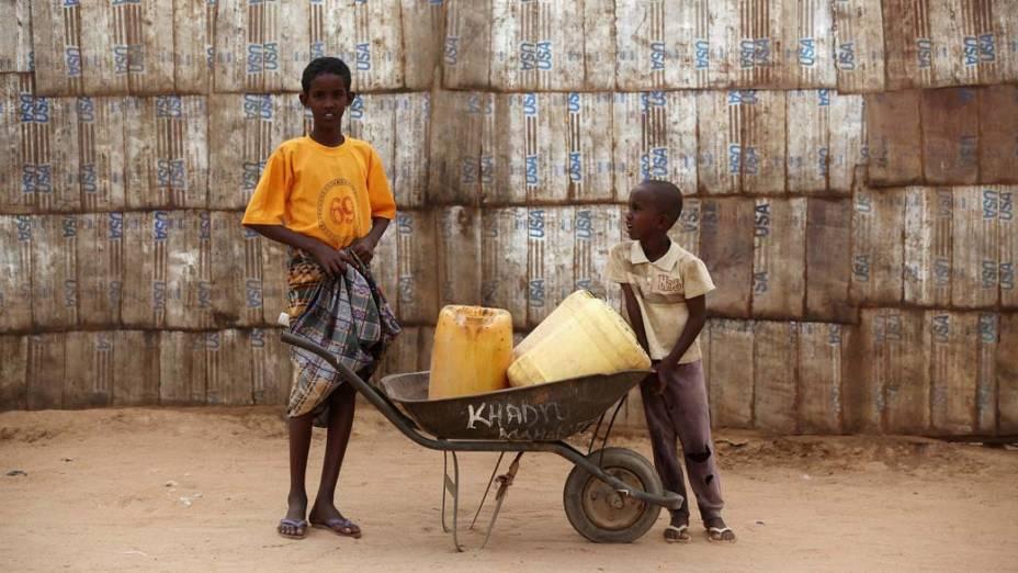 Garotos carregam recipientes com água em Dagahaley, no campo de refugiados de Dadaab, Quênia