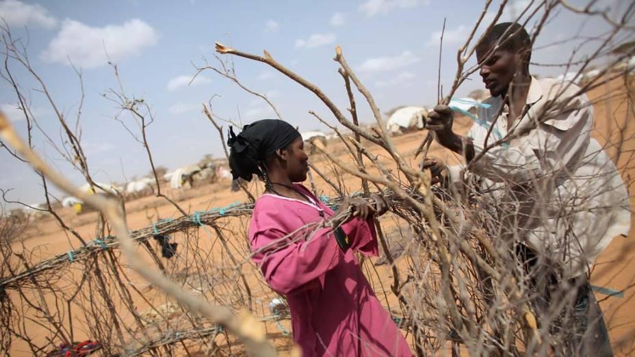 Casal somali constrói sua cabana em Dagahaley, no campo de refugiados de Dadaab, Quênia