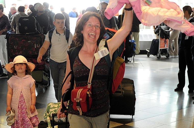 Turista alemã que passou férias na Espanha comemora chegada ao aeroporto de Munique, na Alemanha.