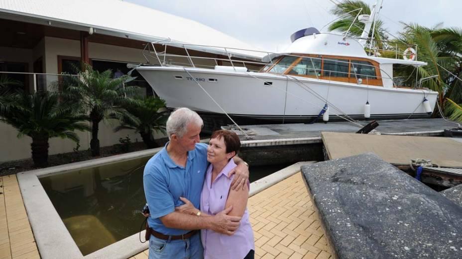 """Casal em sua casa na cidade de Cardwell, Austrália, depois que sua lancha foi jogada para dentro da piscina pelo ciclone """"Yasi"""""""