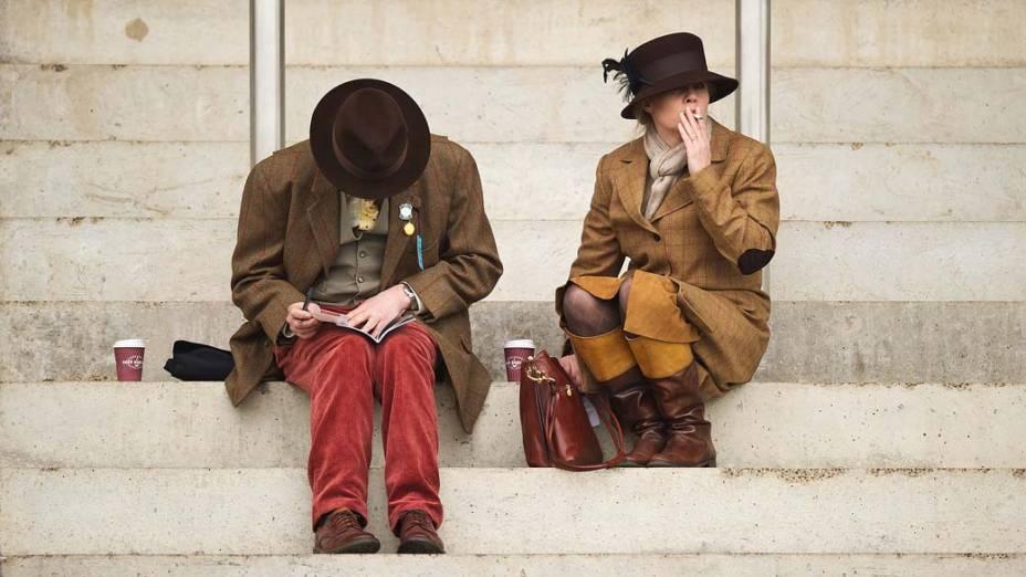 Na cidade de Gloucesteshire, Inglaterra, casal aguarda o início da corrida de cavalos no segundo dia do Festival Cheltenham