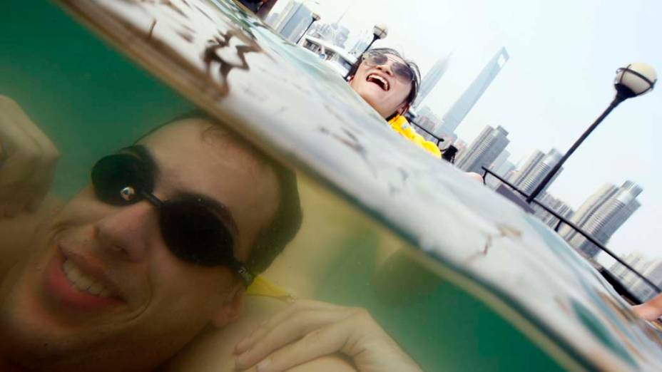 Casal aproveita dia quente em piscina na cidade chinesa de Xangai