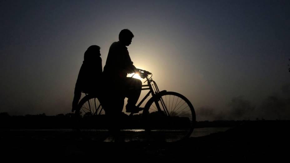 Casal anda de bicicleta na margem do rio Ravi, no Paquistão
