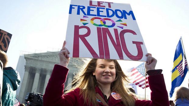 """Apoiadora do casamento gay em frente à Suprema Corte dos EUA.No cartaz, a frase: """"deixe a liberdade ressoar"""", em uma brincadeira com a palavra 'ring', que também significa anel, aliança"""