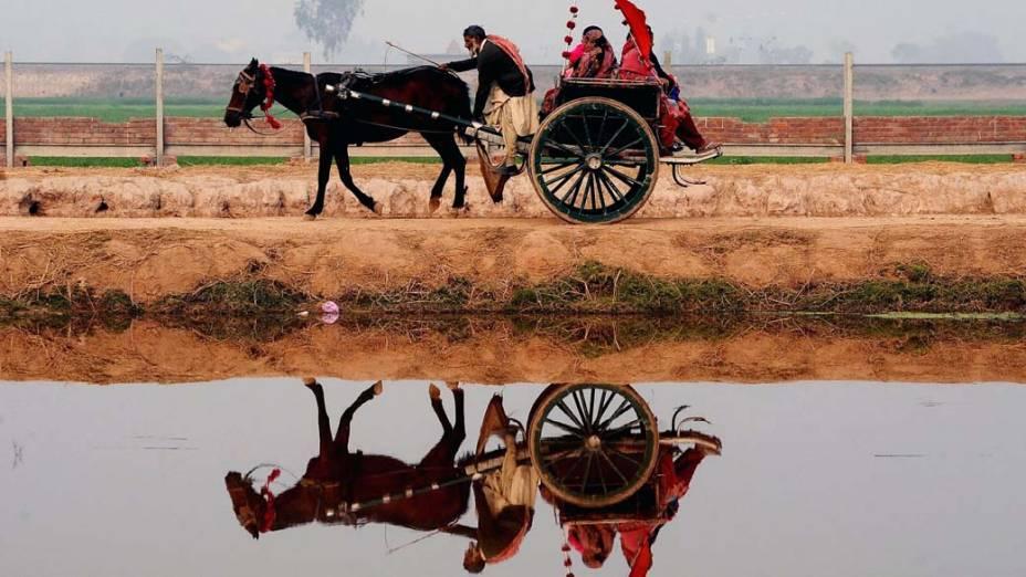 Aldeões paquistaneses viajam em carroça nos arredores de Lahore, Paquistão