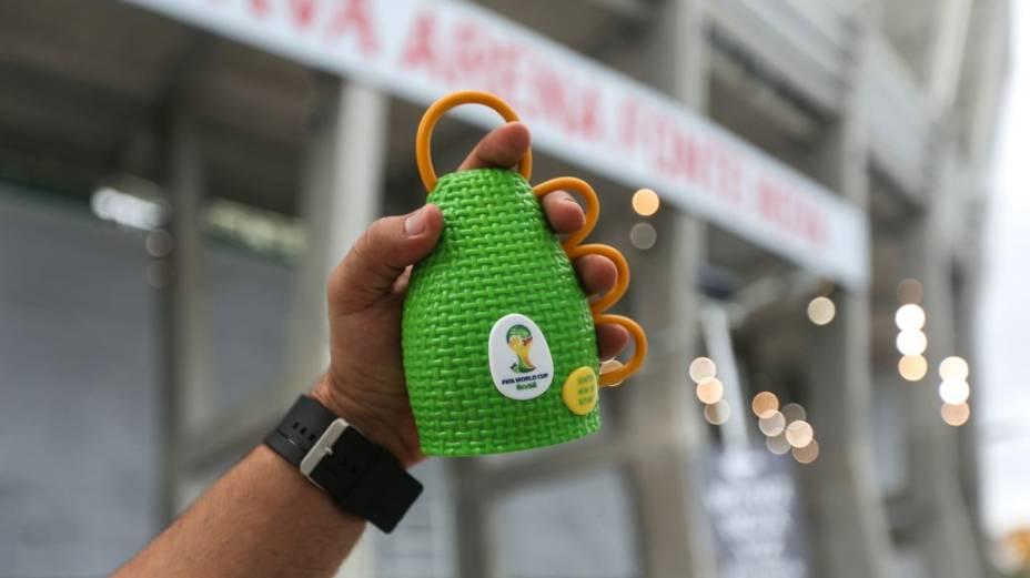 Torcedor segura uma caxirola diante da Arena Fonte Nova, em Salvador