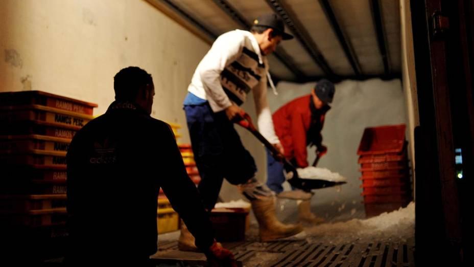 Homens trabalham em caminhão carregado de gelo