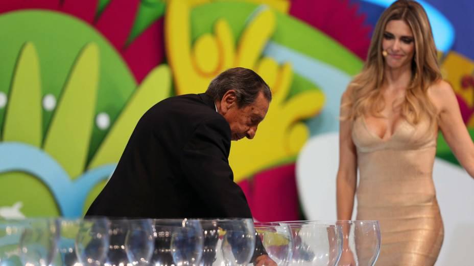 Fernanda Lima observa o ex-jogador uruguaio, Gigghia sorteando uma bolinha