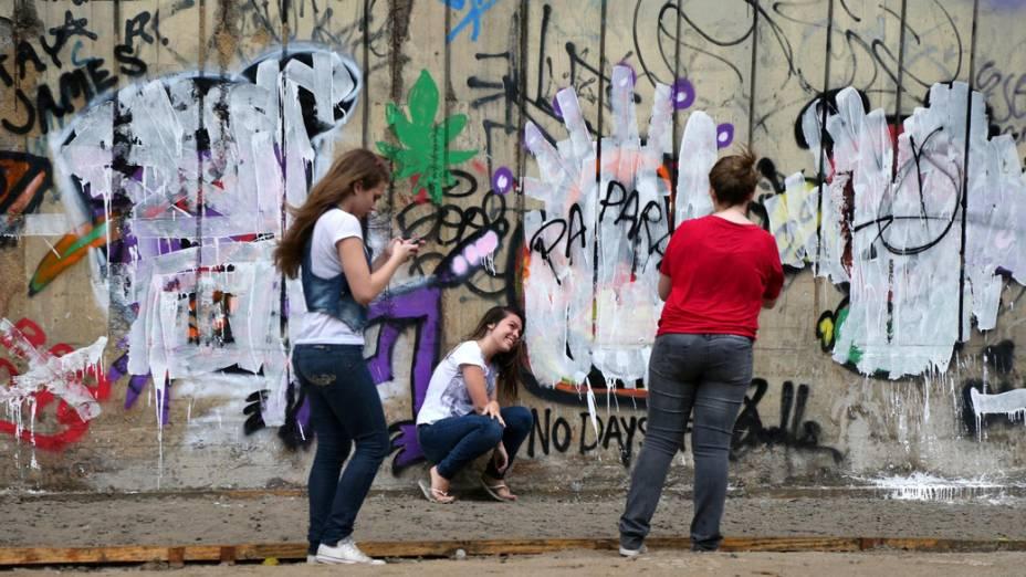 Fãs tiram fotos ao lado dos grafites de Justin Bieber, após um fotógrafo pintar o muro de branco
