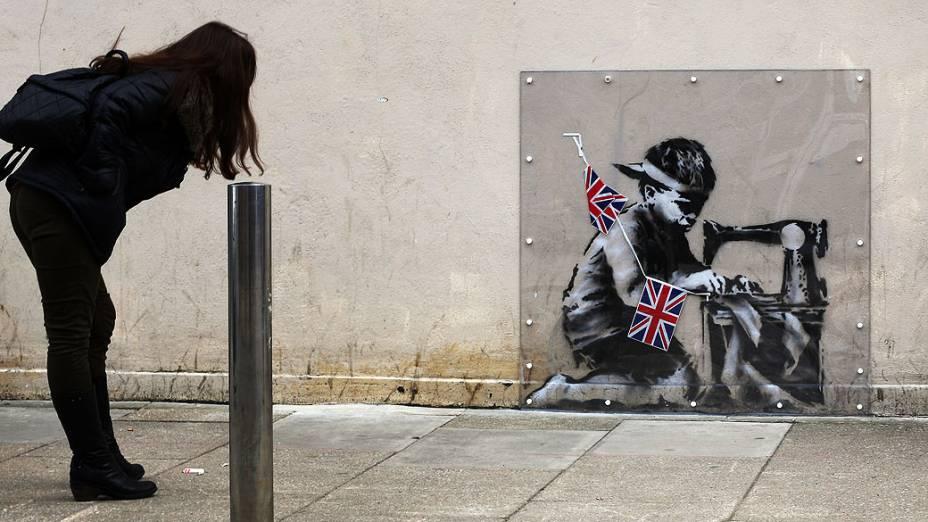 Mulher olha para uma obra do artista Banksy sob uma tampa de plástico em Londres, Inglaterra