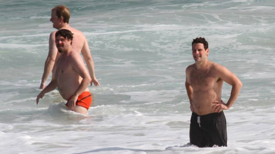 Justin Bartha e Zach Galifianakis entram no mar, na praia da zona sul do Rio