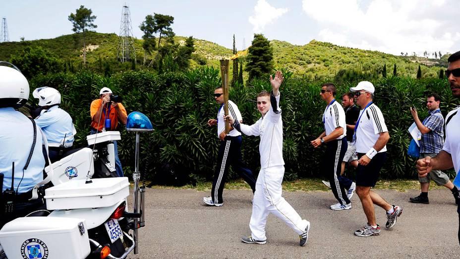 Alexander Loukos, boxeador inglês de descendência grega, corre com a tocha olímpica durante cerimônia na cidade antiga de Olímpia, Grécia