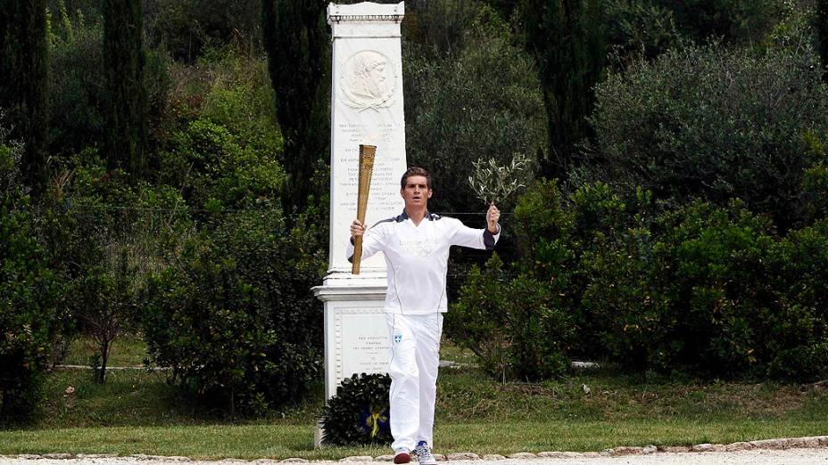 Spyridon Gianniotis, grego campeão mundial de natação com a tocha e um ramo de oliveira durante cerimônia na cidade antiga de Olímpia, Grécia
