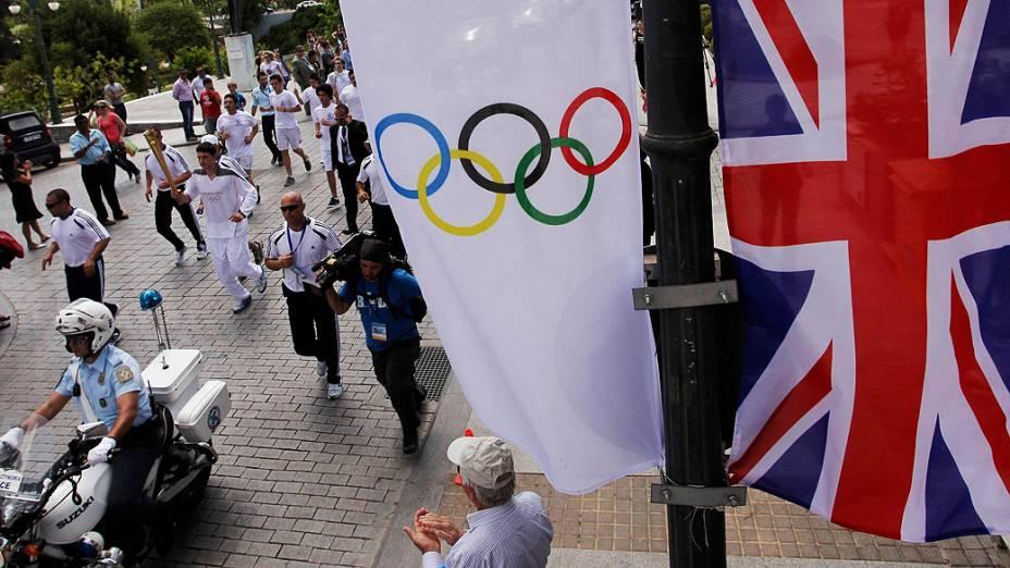 Estudante grego e jogador de basquete, Chris Theodoropolus, corre pelas ruas da cidade antiga de Olímpia com a tocha olímpica