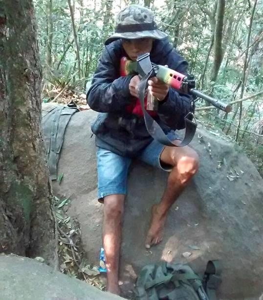 O criminoso identificado como CH exibe um fuzil estilizado nas cores do Reggae na mata da favela