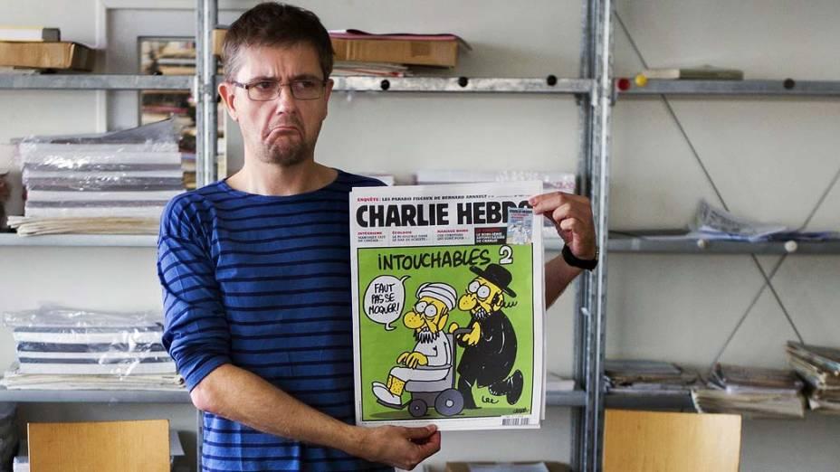 Editor do satírico Charlie Hebdo conhecido apenas como Charb exibe a última edição da revista, que traz na capa uma charge sobre o Islã. A França anunciou que fechará temporariamente embaixadas e escolas em 20 países após a publicação