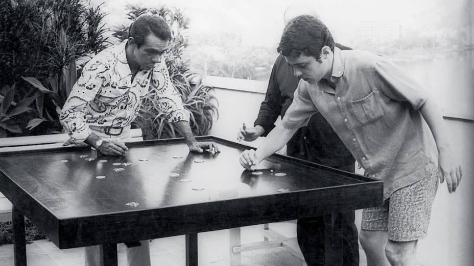 Chico Anysio, jogando futebol de botão contra Chico Buarque de Hollanda, como juiz, Vinicius de Moraes, em 1970.