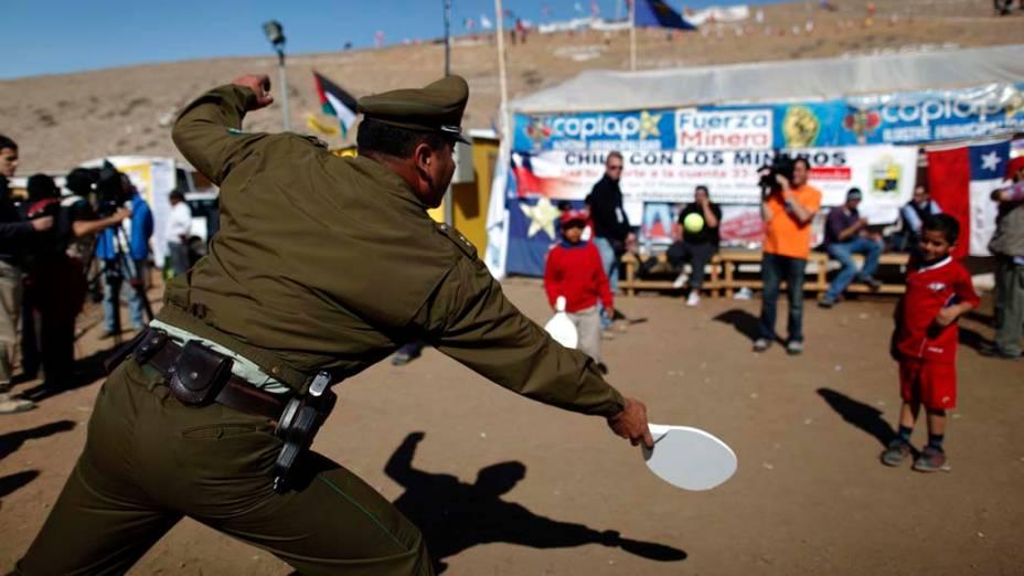 Policial brinca com criança na mina San José enquanto aguarda pela operação de resgate dos mineiros