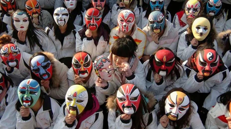 Estudantes com máscaras em evento para promover a ópera Peking em universidade de Liaocheng, China