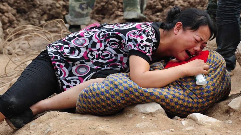 Mulher chora sobre corpo de seu filho, morto em Zhouqu, na China. O país sofre com deslizamentos decorrentes das chuvas, que já mataram 700 pessoas e deixaram cerca de 1000 desaparecidos