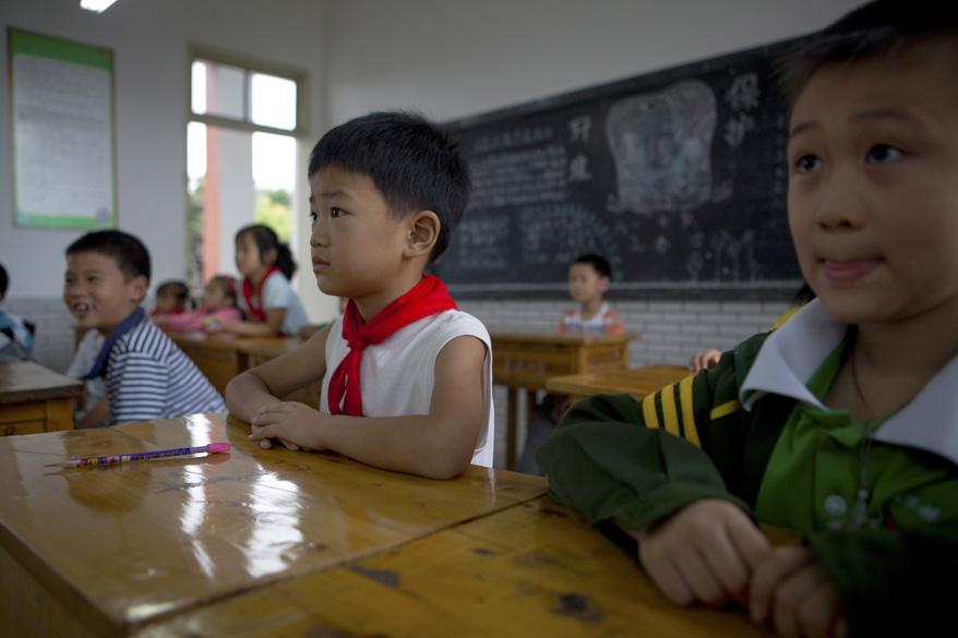 """Os estudantes da escola He Chuan Yucai entoam canções maoístas e dormem sobre travesseiros com a inscrição: """"Nós somos a próxima geração do Partido Comunista"""""""