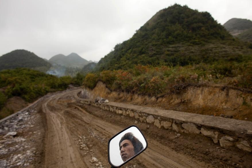 De moto, homem deixa sua vila em Heshan, na província de Guizhou, para ir trabalhar na cidade
