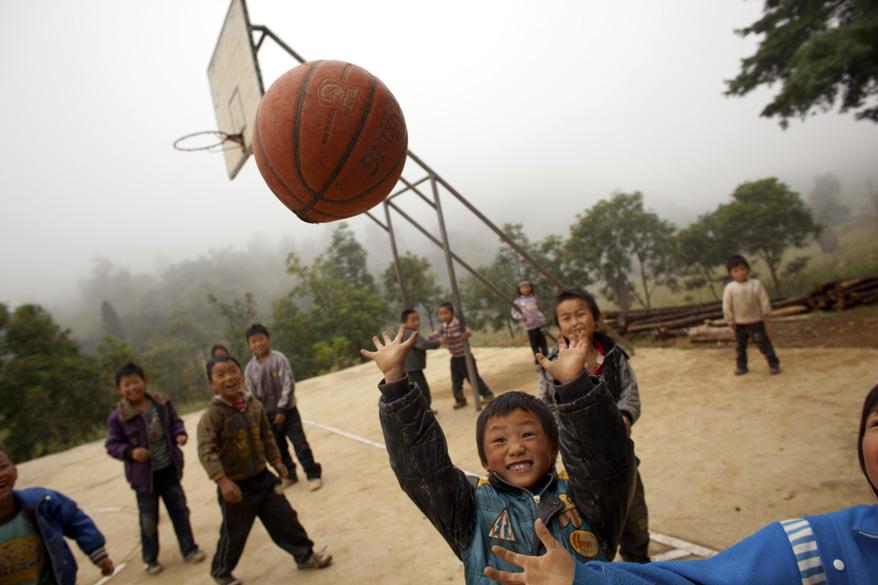 Crianças da única escola de Heshan jogam basquete no intervalo das aulas. A maioria é filha de trabalhadores que migraram para as cidades. As que têm mais sorte recebem a visita dos pais uma vez por ano