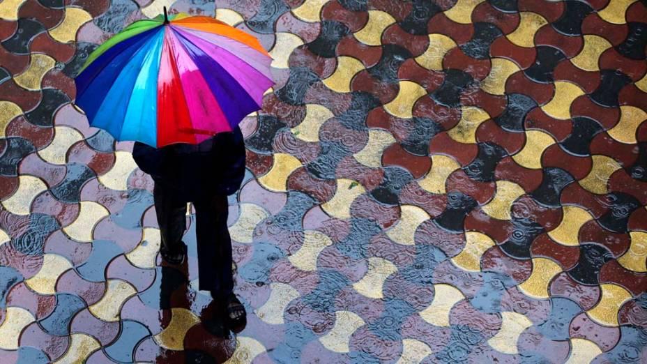 Homem se protege da chuva em Mumbai, Índia