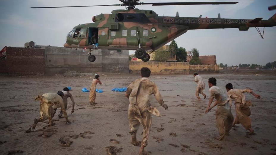 No Paquistão, moradores correm para pegar garrafas d'água distribuidas pela Força Aérea